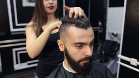 El peluquero de la muchacha hace el peinado al hombre barbudo almacen de metraje de vídeo