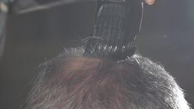 El peluquero de la mujer afeita una cabeza del hombre calvo Primer: El peluquero hace peinado al hombre calvo almacen de video