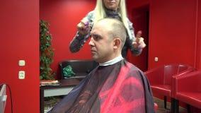 El peluquero de la mujer cortó al cliente del hombre en propia barbería 4K metrajes