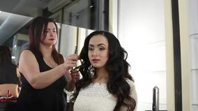 El peluquero de sexo femenino está haciendo las ondas de una Chicago para una morenita hermosa con el pelo largo metrajes