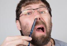 El peluquero de sexo masculino corta su propio pelo en la nariz, mirando la cámara como el espejo peluquero profesional elegante Foto de archivo