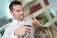 El peluquero de sexo masculino hace el corte para el peluquero rubio del varón de la muchacha Fotos de archivo libres de regalías