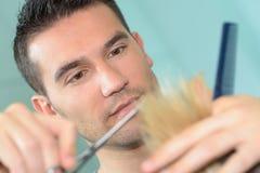 El peluquero de sexo masculino hace el corte para el peluquero rubio del varón de la muchacha Foto de archivo