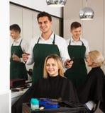 El peluquero de sexo masculino hace el corte para la muchacha rubia Fotografía de archivo