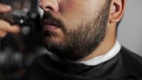 El peluquero de Tattoed esquila la barba del ` s del cliente usando el condensador de ajuste en la peluquería de caballeros, el c almacen de metraje de vídeo