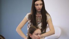 El peluquero en blusa con la impresión floral crea el peinado para la chica joven almacen de metraje de vídeo