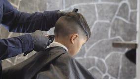 El peluquero en guantes negros afeita cuidadosamente la nuca de un niño asiático en fps de una peluquería de caballeros 60