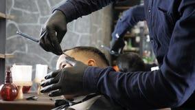 El peluquero en guantes negros afeita cuidadosamente el whisky con una maquinilla de afeitar recta a los fps asiáticos de un niño
