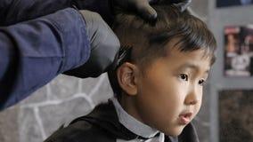 El peluquero en guantes negros afeita fps asiáticos del whisky 60 del niño