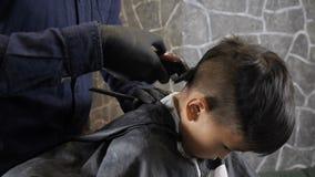 El peluquero en guantes negros afeita la parte posterior asiática del niño de los 60 fps principales