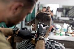 El peluquero en guantes negros afeita los pelos del hombre en la parte posterior en una peluquería de caballeros fotografía de archivo libre de regalías