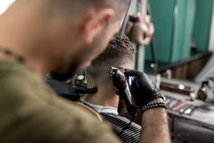 El peluquero en guantes negros afeita los pelos del hombre en la parte posterior en una peluquería de caballeros foto de archivo libre de regalías