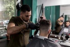 El peluquero en guantes negros afeita los pelos del hombre en el lado en un peluquero detrás imagenes de archivo