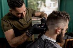 El peluquero en guantes negros afeita los pelos del hombre en el lado en un peluquero detrás fotografía de archivo libre de regalías
