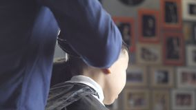 El peluquero en guantes negros afeita el pelo en la nuca de los fps asiáticos de un muchacho 60