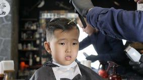 El peluquero en guantes negros afeita suavemente fps asiáticos del muchacho 60 de las explosiones