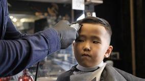 El peluquero en guantes negros afeita suavemente fps asiáticos del niño 60 de las explosiones