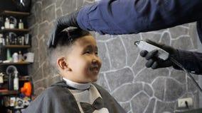 El peluquero en guantes negros afeita suavemente fps asiáticos felices del niño 60 de las explosiones