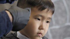 El peluquero en guantes negros afeita suavemente fps asiáticos tristes del whisky 60 del niño