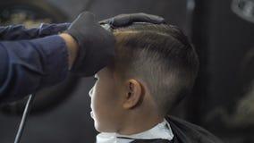 El peluquero en guantes negros afeita una partida en el jefe de los fps asiáticos de un niño 60