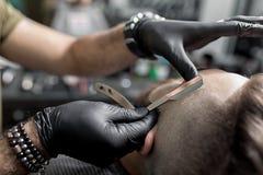 El peluquero en guantes negros arregla el templo del hombre joven barbudo brutal con una maquinilla de afeitar recta en una barbe foto de archivo libre de regalías