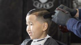 El peluquero en guantes negros asperja el agua en el pelo de un niño asiático y los peina 60fps