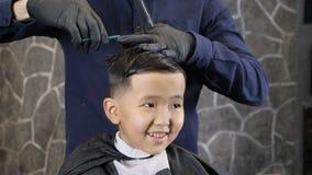 El peluquero en guantes negros corta el pelo en la corona de los fps asiáticos de un niño 60