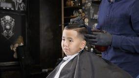 El peluquero en guantes negros peina el pelo a un niño asiático y camina alrededor de él 60 fps