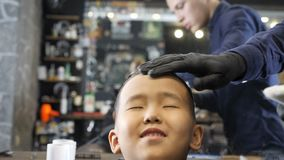El peluquero en guantes negros quita el pelo del corte de la frente de un niño asiático con los fps de un cepillo 60