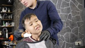 El peluquero en guantes negros quita el pelo del cuello de los fps asiáticos de un niño 60