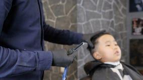 El peluquero en guantes negros se está preparando para afeitar la maquinilla de afeitar recta de los fps asiáticos de un niño 60