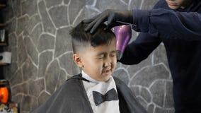 El peluquero en guantes negros seca al muchacho asiático con los fps del secador de pelo 60