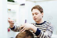 El peluquero en el salón de belleza hace un corte de pelo fotos de archivo