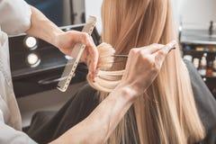 El peluquero está cortando el pelo largo en salón de pelo fotos de archivo libres de regalías