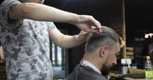 El peluquero está poniendo fin al pelo del hombre envejecido centro que usa un cepillo para el pelo y las tijeras almacen de metraje de vídeo