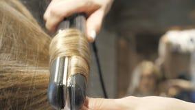 El peluquero est? enderezando el pelo del cliente en un sal?n de belleza metrajes
