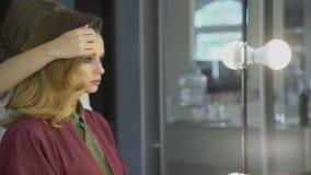 El peluquero experimentado toca el peinado de la señora que se sienta en salón metrajes