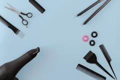 El peluquero fijó con los diversos accesorios en fondo azul Imágenes de archivo libres de regalías