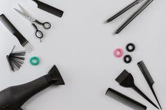 El peluquero fijó con los diversos accesorios en fondo gris Foto de archivo libre de regalías
