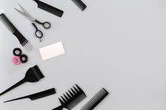 El peluquero fijó con los diversos accesorios en fondo gris Fotografía de archivo