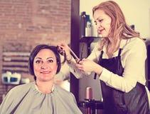 El peluquero hace al corte de pelo de la mujer con el uso de tijeras y del hairb Fotos de archivo
