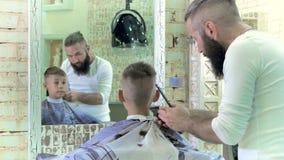 El peluquero hace al niño pequeño del peinado en la barbería almacen de metraje de vídeo
