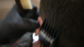 El peluquero hace corte de pelo con las podadoras de pelo del condensador de ajuste en la barbería, primer de la cabeza del ` s d almacen de video