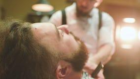 El peluquero hace el corte o diseñar de una barba almacen de metraje de vídeo