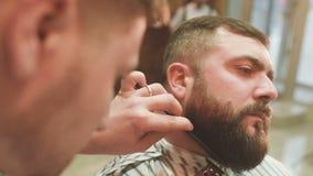 El peluquero hace el corte o diseñar de una barba almacen de video