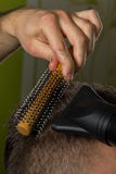 El peluquero hace el pelo con el cepillo y el hairdryer del cliente en salón profesional de la peluquería fotografía de archivo libre de regalías
