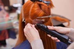El peluquero hace extensiones del pelo a una muchacha joven, pelirroja, en un salón de belleza foto de archivo