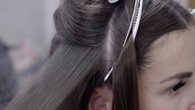 El peluquero hace la laminación del pelo en un salón de belleza para una muchacha con el pelo moreno almacen de metraje de vídeo
