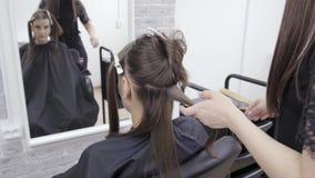 El peluquero hace la laminación del pelo en un salón de belleza para una muchacha con el pelo moreno Concepto del cuidado del cab almacen de metraje de vídeo