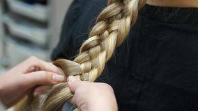 El peluquero hace a la muchacha del blonde del peinado Proceso del Hairstyling almacen de metraje de vídeo